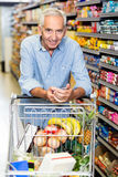 Senior man using phone at grocery store. While pushing cart royalty free stock images