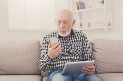 Senior man using phone and tablet. Sitting on sofa at home. Modern technology, communication concept Royalty Free Stock Photos