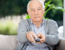 Senior Man Using Remote Control While Sitting On Stock Images