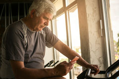 Senior man using smart phone in the gym. Royalty Free Stock Images