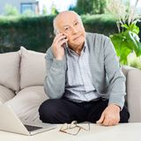Senior Man Using Smartphone At Nursing Home Porch Stock Photo