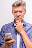 Senior man. Is using smartphone, standing on white background royalty free stock photos