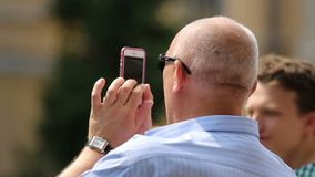 Senior man using smartphone with touchscreen to take photo, modern technologies. Stock footage stock video footage