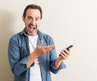 Handsome senior man at home. Senior man using smartphone very happy pointing with hand and finger Stock Photography