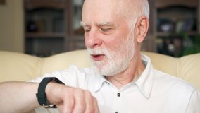 Senior man at home using smartwatch, browsing, reading news. Concept of technology use by older people. Senior man using smartwatch, browsing, reading news stock footage