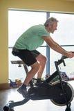 Senior man using a spinning bike Royalty Free Stock Photo