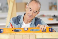 Senior man using spirit level on piece wood stock photos