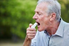 Senior man using a spray as medicine. Old man using a spray as a medicine for hay fever in nature Royalty Free Stock Photography