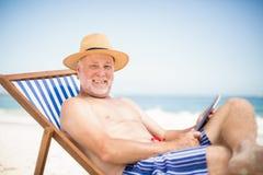 Senior man using tablet at the beach Stock Photos