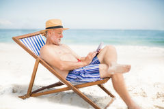 Senior man using tablet at the beach. On a sunny day Royalty Free Stock Image