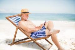 Senior man using tablet at the beach Royalty Free Stock Image