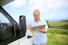 Senior man using tablet by camping car stock image