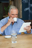 Senior man using tablet computer while drinking coffee. At table in cafe Royalty Free Stock Images