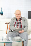 Senior man using tablet computer at. Home in the living room Stock Photo