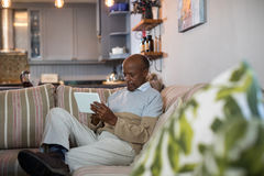 Senior man using tablet computer in living room. Senior man using tablet computer while sitting on sofa in living room at home Stock Images