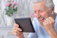 Senior man using tablet. Happy senior man using tablet, close up view Royalty Free Stock Image