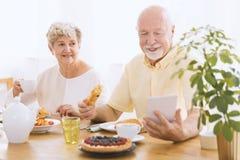 Senior man using tablet. Happy elderly couple eating breakfast together. Senior man reading news using tablet Royalty Free Stock Photo