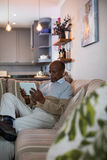 Senior man using tablet at home. Senior man using tablet while sitting on sofa at home Royalty Free Stock Images