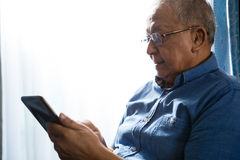 Senior man using tablet at nursing home. Senior man using tablet by window at nursing home Stock Photos