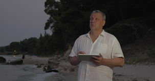 Senior man using tablet PC on beach in late evening stock footage