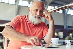 Senior man using tablet pc in cafe Stock Image