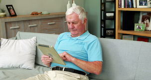 Senior man using tablet pc. On couch stock video footage