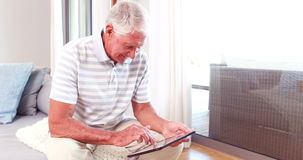 Senior man using tablet pc. On couch stock footage