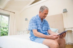 Senior man using tablet pc. At home in bedroom Stock Photos