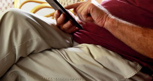 Senior man using tablet pc while sitting in rocking chair. In retirement home stock video