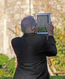 Senior man using tablet. Photo of a senior man using his tablet to take photos of whitstable castle in kent Stock Photography