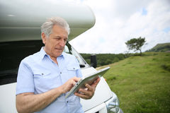 Senior man using tablet while travelling Stock Photography