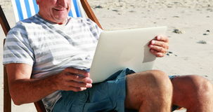 Senior man video chatting on laptop at beach stock video footage