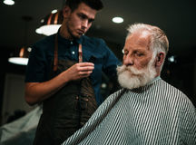Senior man visiting hairstylist in barber shop. Senior men visiting hairstylist in barber shop Stock Image