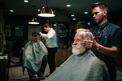 Senior man visiting hairstylist in barber shop. Senior men visiting hairstylist in barber shop Stock Photos