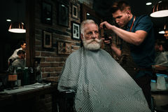 Senior man visiting hairstylist in barber shop. Senior men visiting hairstylist in barber shop Royalty Free Stock Image