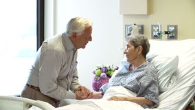 Senior Man Visiting Wife In Hospital Room. Senior woman is pleased to see husband as he visits her in hospital.Shot on Sony FS700 in PAL format at a frame rate stock footage