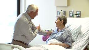 Senior Man Visiting Wife In Hospital Room