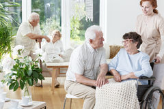 Senior man visits his smiling wife. Senior men visits his smiling wife on wheelchair at friendly senior home royalty free stock images