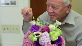 Senior Man Visits Wife In Hospital Room With Flowers. Camera follows senior man as he visits wife in hospital bed and gives her bunch of flowers.Shot on Sony stock footage