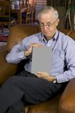 Senior man w/blank book. Senior man with blank book in upscale home. Work path for book--just drop in your title Royalty Free Stock Images