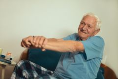 Senior Man Waking Up And Stretching. In Bedroom Stock Photos