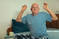 Senior Man Waking Up And Stretching. In Bedroom Stock Image