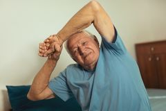 Senior Man Waking Up And Stretching. In Bedroom Royalty Free Stock Photo