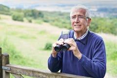Senior Man On Walk With Binoculars. Senior Man Walking With Binoculars Stock Photo