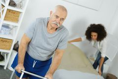Senior man with walker at home with home help woman stock photo