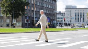 Senior man walking along city crosswalk stock video footage