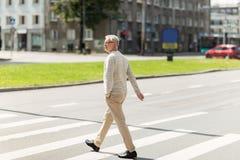 Senior man walking along city crosswalk. Leisure and people concept - senior man walking along summer city crosswalk Royalty Free Stock Photos