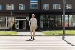 Senior man walking along city crosswalk Royalty Free Stock Image
