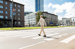 Senior man walking along city crosswalk Stock Image