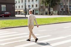 Senior man walking along city crosswalk Stock Photography